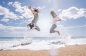 Dvě dívky skok do písku pláže