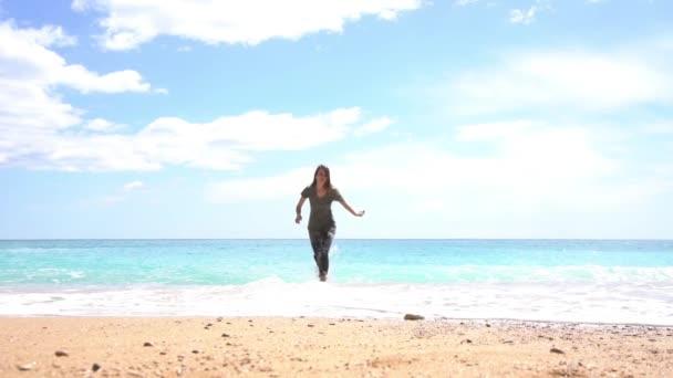 Dívka skáče na písku na pláži