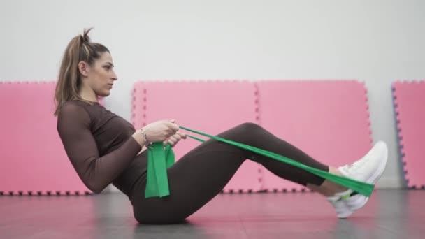 Krásná žena v tělocvičně cvičení s elastickými kapelami.