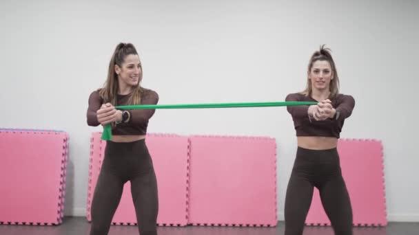 Dvě dvojčata v tělocvičně cvičení s gumičkou.