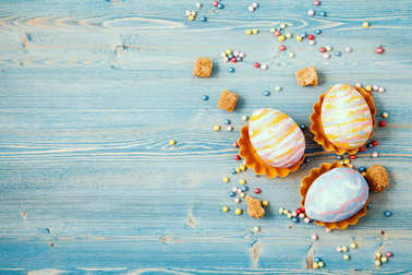 Easter multicolored eggs on a blue wooden background. Background for a postcard, Easter concept, space for text.
