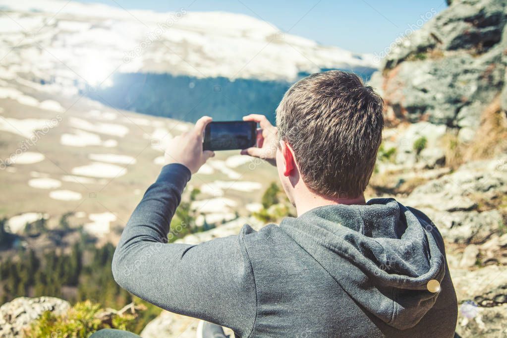 travel guy sits on top of the mountain and takes pictures of the smartphone View from back of the tourist traveler on background mountain