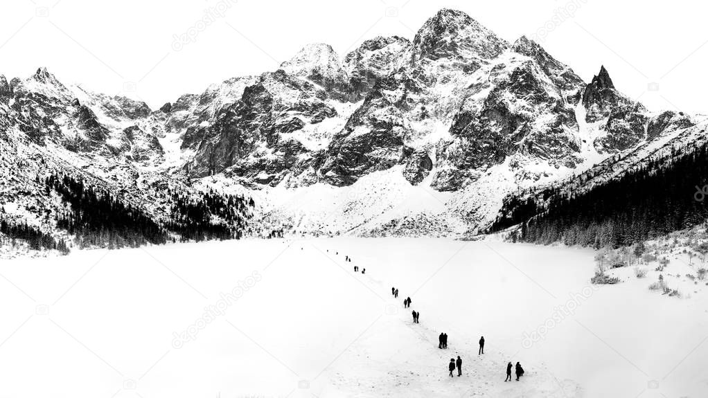 Black and white winter landscape of frozen Morskie Oko Lake and snowy Tatra Mountains in Lesser Poland.