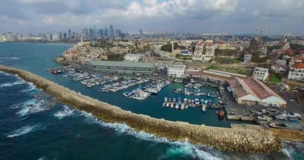 Letecký pohled a horizontální pohyb, létání nad lodě kotvící v přístavu Jaffa a lidí jedoucích podél pobřeží v zamračený den. Tel Avivu Panorama městských mrakodrapů na pozadí