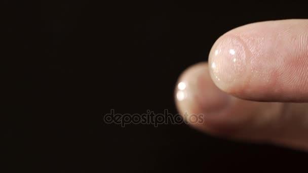 Prst s černým pozadím a kontaktní čočky