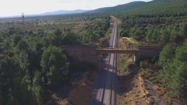 Horský cyklista přes most přes trať