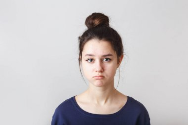 portrait of a pimply teenage girl in a blue T-shirt on a gray background, sad face