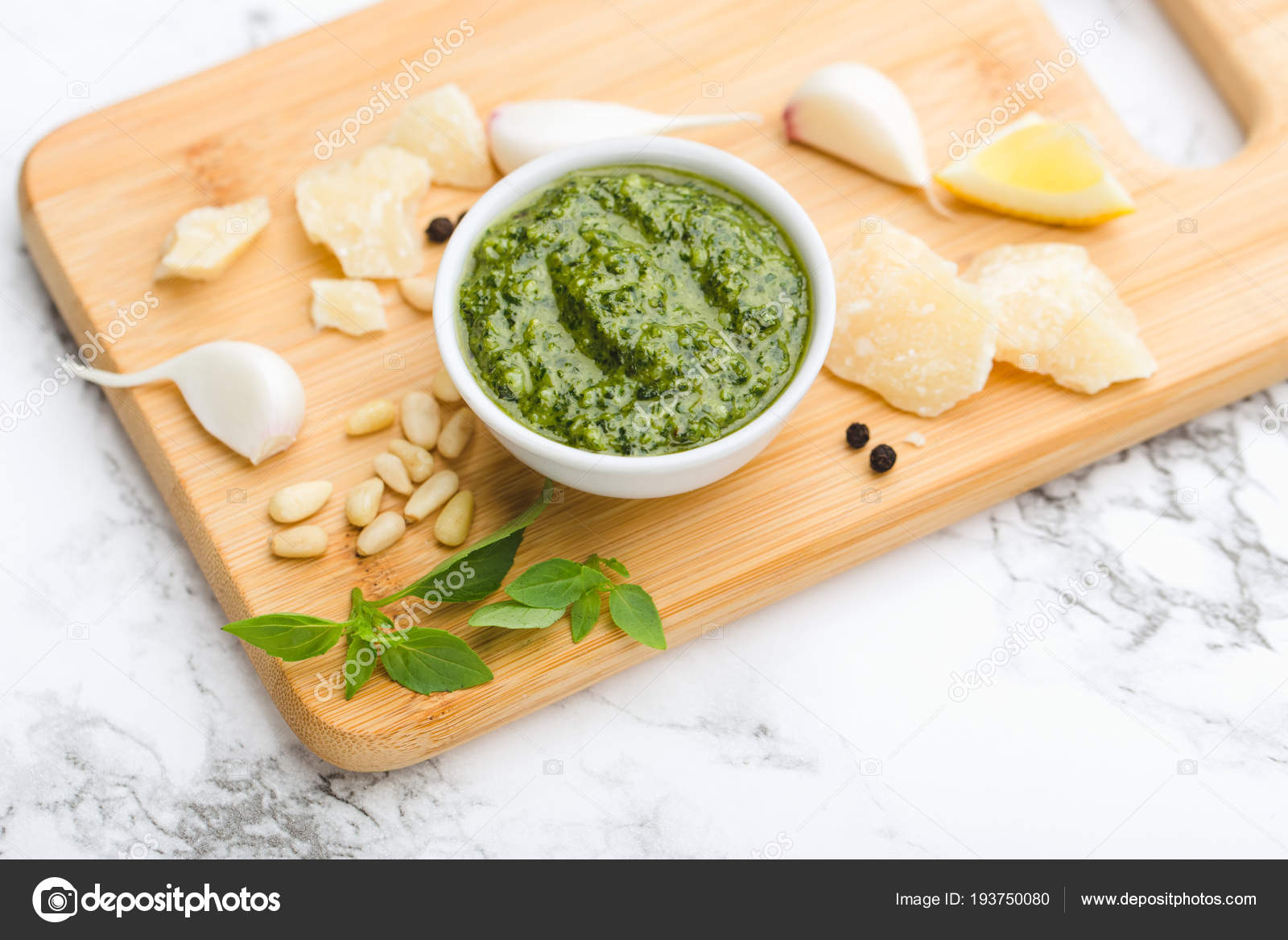 On A Marble Table Wooden Cutting Board In Round Cup Green Pesto Sauce