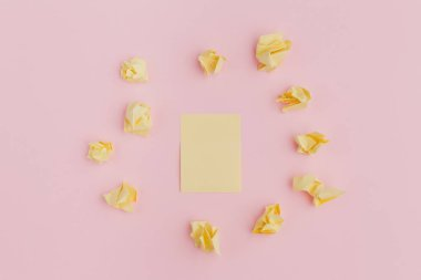 a bunch of crumpled yellow stickers of paper, scattered on a pink background, in the center of a clean sheet. office style