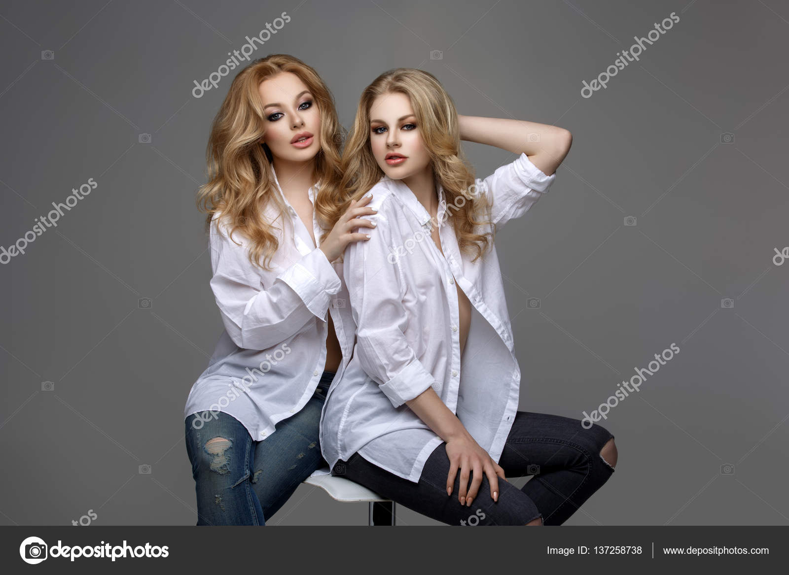 dos chicas guapas en camisas blancas y pantalones vaqueros u foto de stock