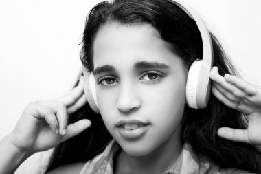 Afro-American little girl with headphones listening to music