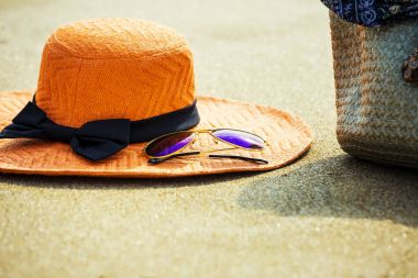 Hat, sunglasses and bag with on tropical beach