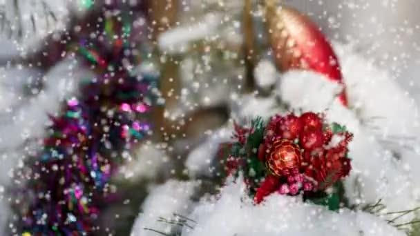 Weihnachtskarte mit rotem Weihnachtsschmuck auf einer schneebedeckten Kiefer an einem frostigen Wintertag.