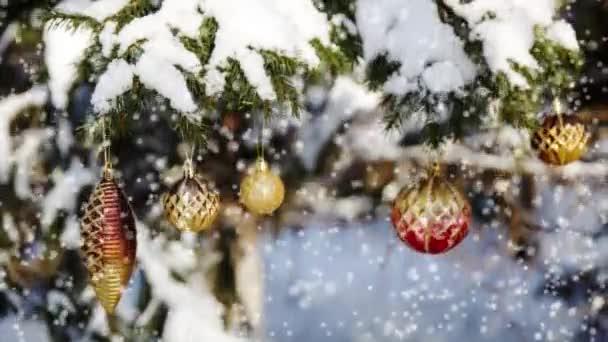 Vánoční přání s ozdoby na vánoční stromeček, pokryté sněhem na mrazivý zimní den.