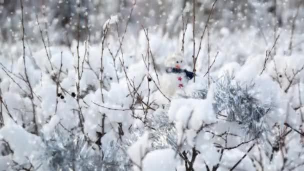 Novoroční karta s malou hračku sněhulák, v křoví bílým sněhem, s stříbrným pozlátko