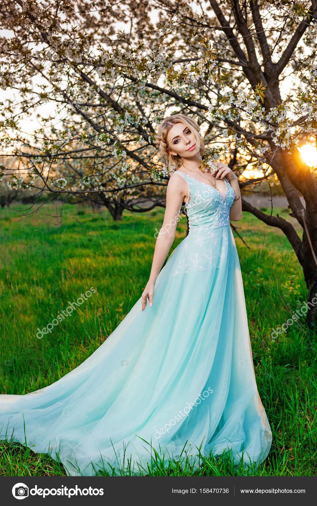Una chica en un vestido largo turquesa posando en el jardín de flor ...