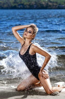 The blonde poses on the seashore in a swimsuit