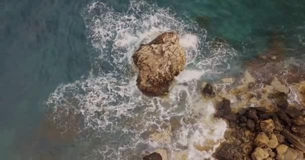 Vlny narážející na skály v moři