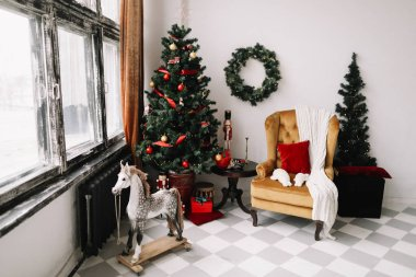 A beautiful living room decorated for Christmas. New Year interior. Decorated fir tree with garlands and balls, festive interior decorations