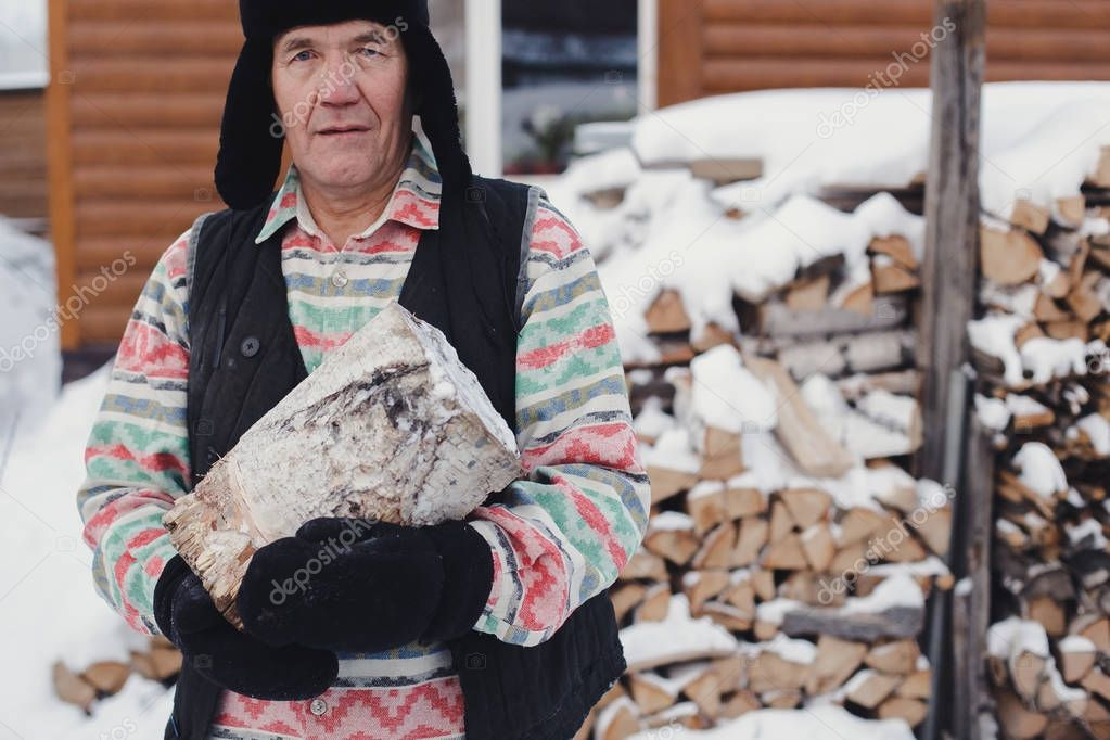 A man in the village holds a log