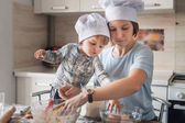 Fotografie mother and child in chef hats preparing dough at kitchen