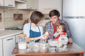 beautiful young family preparing cookies in shape of christmas tree
