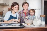 Fotografie šťastná rodina Příprava těsta na domácí sušenky dohromady a při pohledu na fotoaparát