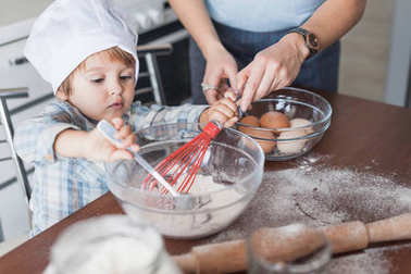 mother and child mixing dough for cookies dough at kitchen