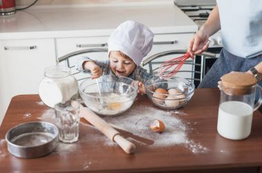 mother and laughing happy child preparing dough at kitchen