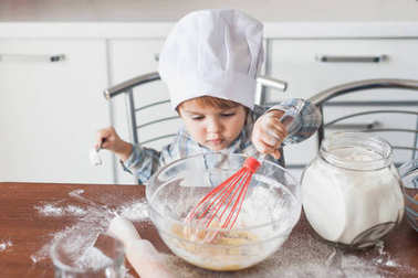 little kid in chef hat mixturing dough with whisk at kitchen