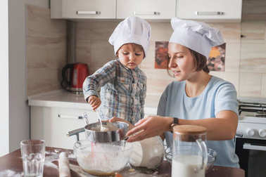 mother and little child in chef hats preparing dough on messy table at kitchen