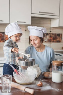 mother and adorable child in chef hats preparing dough on messy table at kitchen