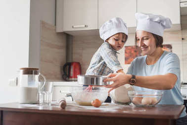 happy young mother and child in chef hats preparing dough at kitchen