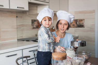 beautiful young mother and child preparing dough for cookies together at kitchen