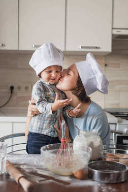 mother kissing her child while they preparing dough at kitchen