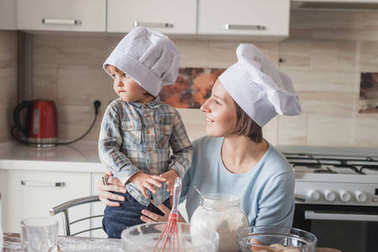 mother and child looking away while preparing dough at kitchen