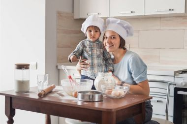 mother and child preparing dough at kitchen and looking at camera