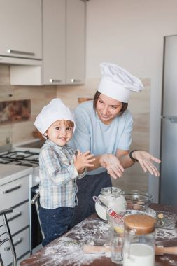 happy young mother and child preparing dough at kitchen