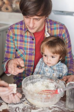 father and child looking at unbaked cookie in hand of mother