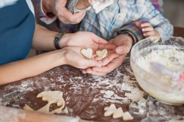 cropped shot of family preparing homemade cookies in shape of heart together
