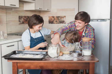 playful young family preparing cookies together at kitchen