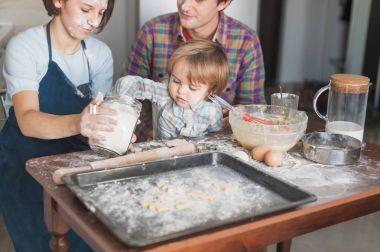 little kid helping his parents with cooking at kitchen