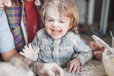 laughing little boy covered with flour while cooking with parents