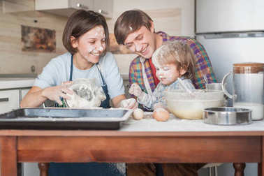 young family spilled with flour cooking together at kitchen