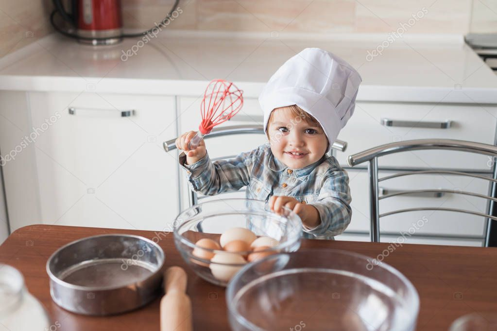 adorable little kid in chef hat with whisk and eggs
