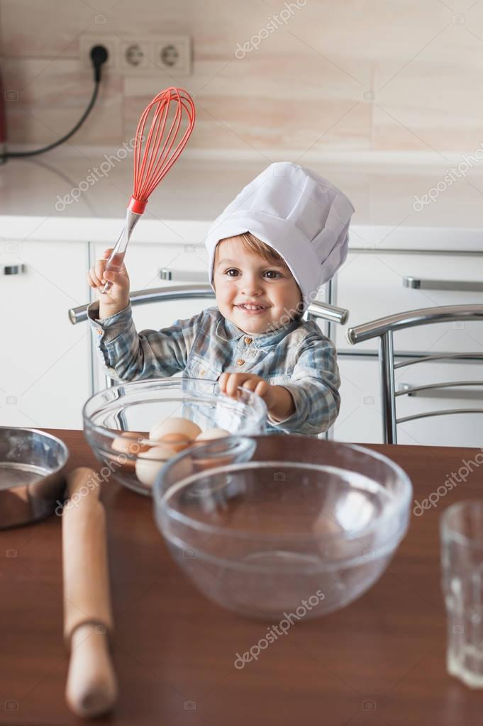 happy little kid in chef hat with whisk and eggs in bowl