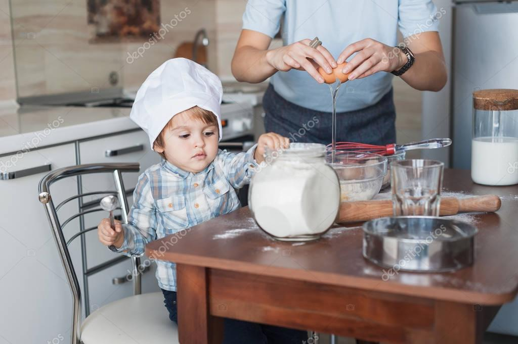 mother and child preparing dough for cookies dough at messy kitchen