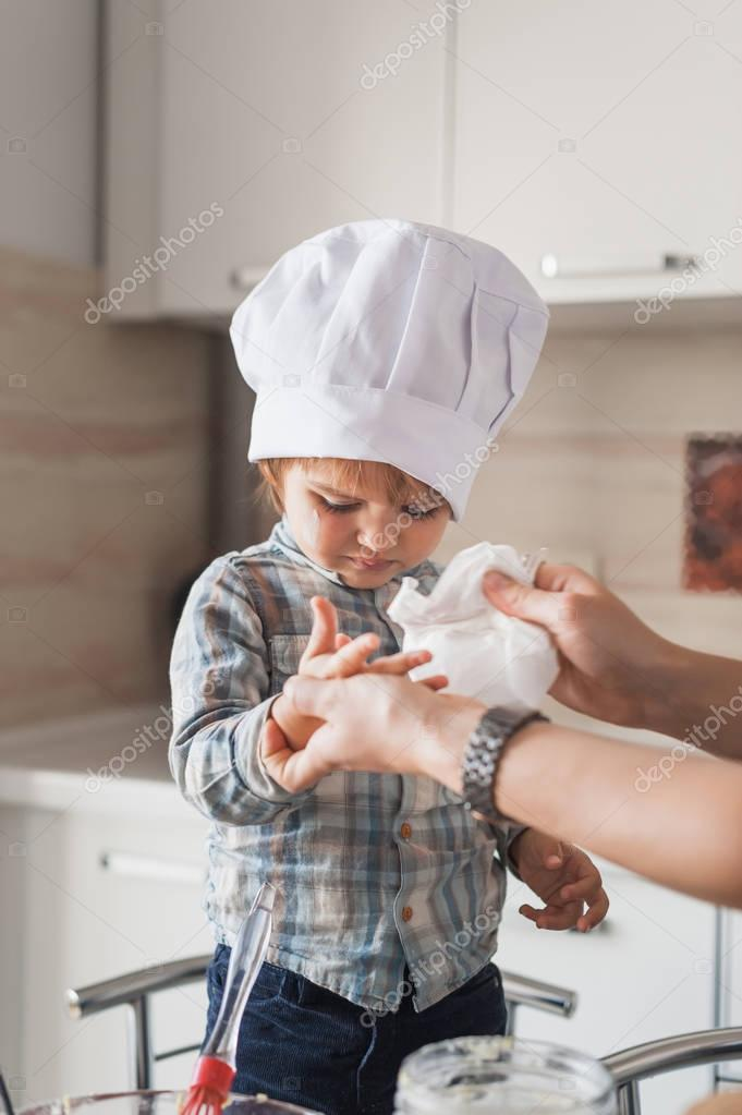 mother cleaning hands of child in chef hat after cooking