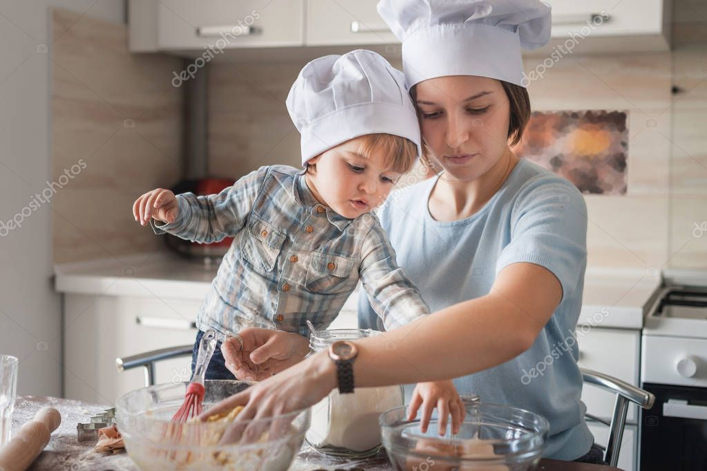 mother and child in chef hats preparing dough at kitchen