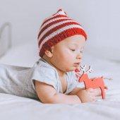 Detailní portrét kojenecké dítěte v pletená pruhovaná čepice s deer hračky v posteli